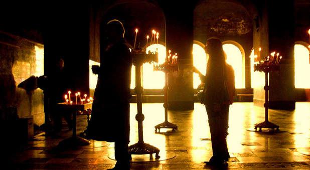 Oameni care se roagă în întuneric cu niște lumânări - imagine preluată de pe charismamag.com