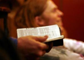 un om ține o Biblie în mână la o întâlnire - imagine preluată de pe christianpost.com
